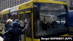 Kiev: șoferul unui autobuz controlează adeverințele pasagerilor, după limitarea dreptului de a folosi transportul în comun, măsură luată pentru a limita răspândirea pandemiei de coronavirus, Ucraina, 5 aprilie 2021.