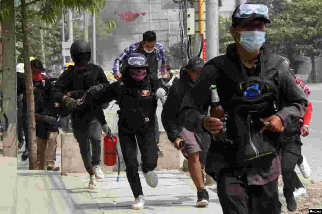 Демонстранти біжать повз барикаду під час протесту проти державного перевороту в М'янмі. Мандалай, 15 березня 2021 року