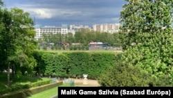 Gesztenyefákkal tarkított látkép: háttérben a Szajna lakóhajói, az OECD kupolás épülete és az Eiffel-torony.