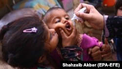 A health worker administers polio vaccine to children during a polio vaccination door-to-door campaign in Karachi on June 7.