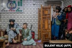 """Тонаушылық жасады деп айыпталған ер адам (сол жақтан екінші) Кабулдағы полиция бөлімінде """"Талибан"""" мүшесінің қасында отыр"""