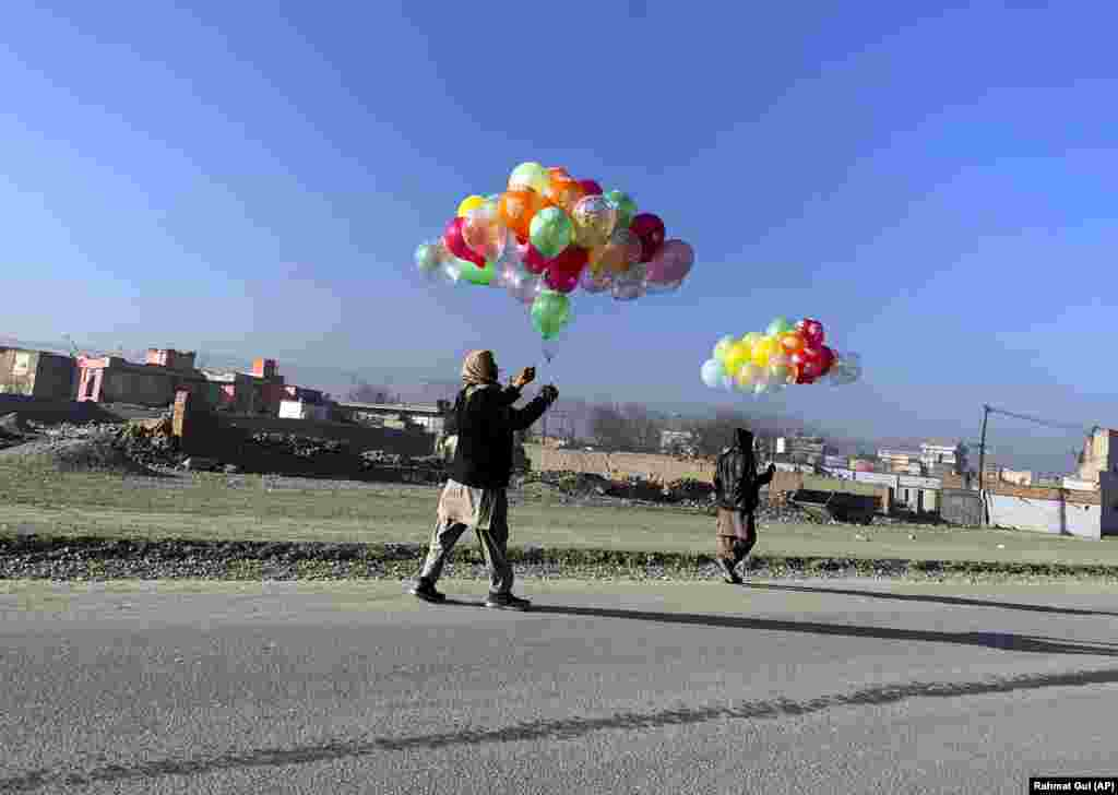 An Afghan man and and a boy walk to sell colored balloons on a street in Kabul. (AP/Rahmat Gul)
