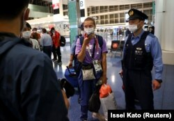 Kristina Țimanovskaia, escortată de ofițeri de polițiști japonezi pe aeroportul internațional Haneda din Tokyo, după ce a cerut ajutorul autorităților japoneze - 1 august 2021