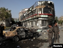Members of Afghan security forces keep watch at the site of a nighttime car bomb blast in Kabul on August 4.