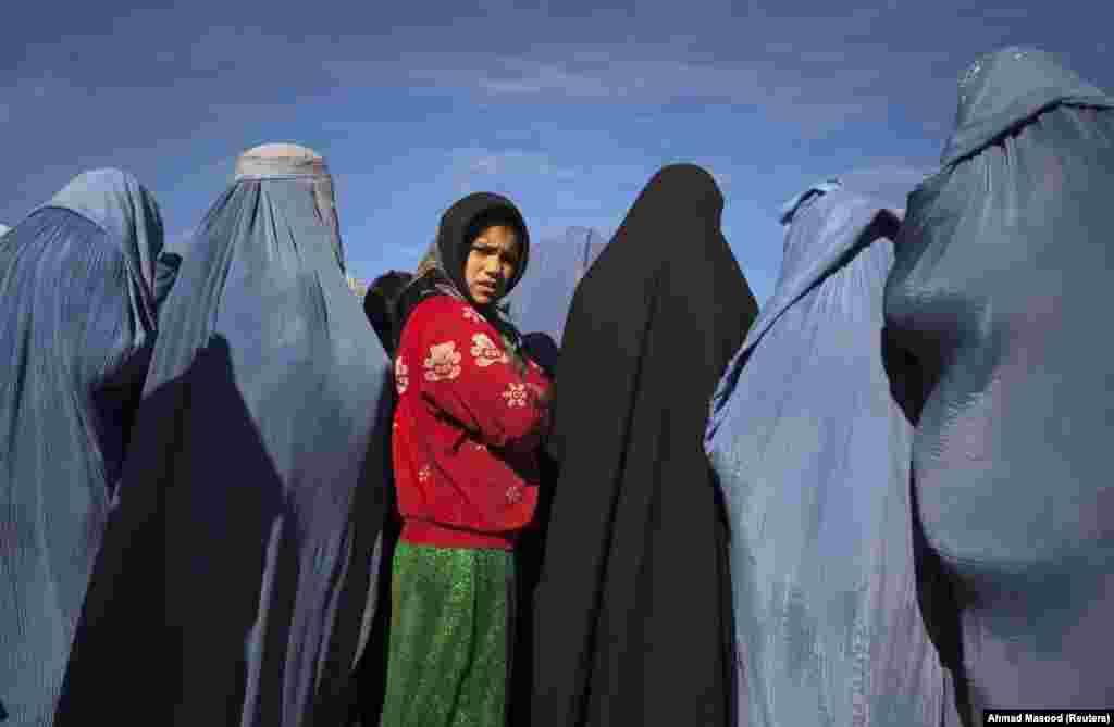 """Девојче од Авганистан стои меѓу вдовици со бурки за време на проектот за вработување на хуманитарната организација """"КАРЕ Интернационал""""."""