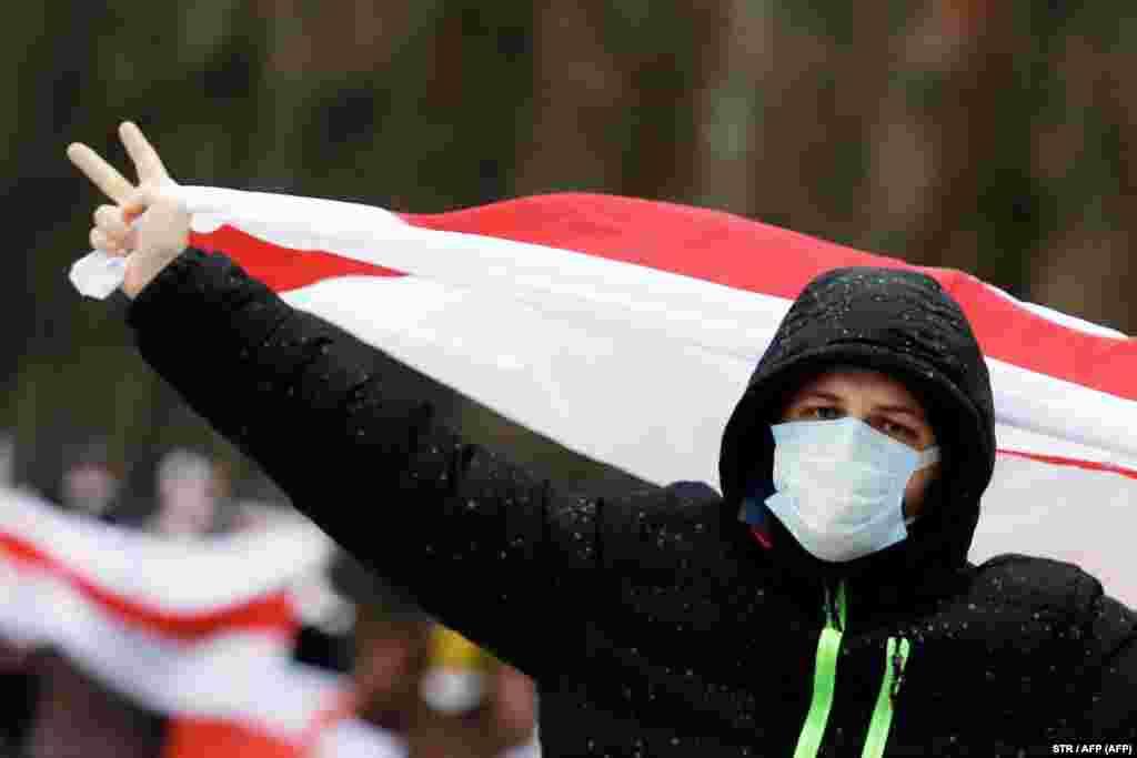 Një burrë duke mbajtur një flamur të dikurshëmtë Bjellorusisë, bardhë e kuq, shihet në protestat në Misk të Bjellorusisë më 13 dhjetor. (AFP)