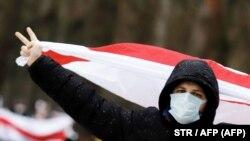 Lukasenka lemondását követelő tüntető zászlóval Minszkben 2020. december 13-án