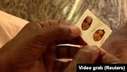 Një prind në Nigeri mban në duar fotografitë e dy vajzave të rrëmbyera.