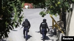Disa zyrtarë policorë shihen duke ecur afër rezidencës së presidenit të vrarë të Haitit, Jovenel Moise.
