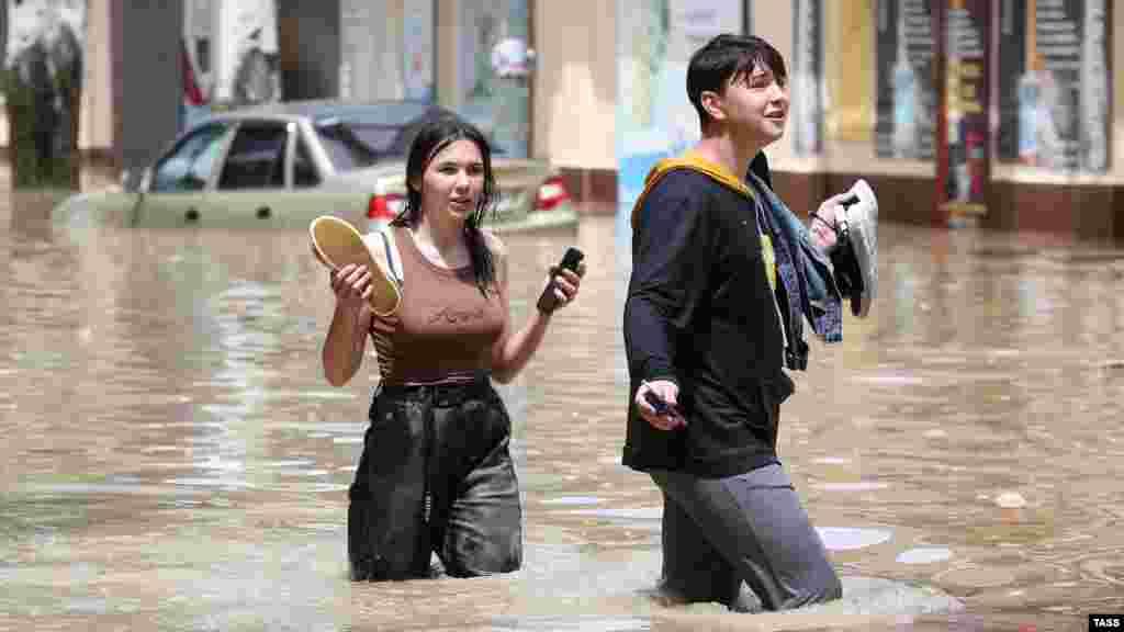 Вода поднялась выше колена. Смельчаки, рискнувшие перейти улицу, передвигаются босиком