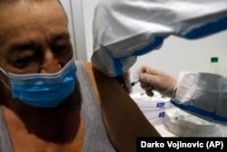 Personal medical administrând o doză de vaccin anti-Covid unui bărbat din Belgrad, 17 februarie.