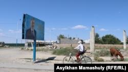 Велосипедист едет мимо баннера с изображением бывшего президента Казахстана Нурсултана Назарбаева. Село Шорнак, Сауранский район, Туркестанская область, 30 июня 2021 года