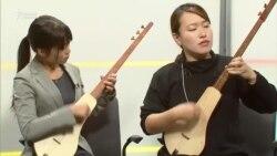 Играющие на комузе волонтеры из Японии