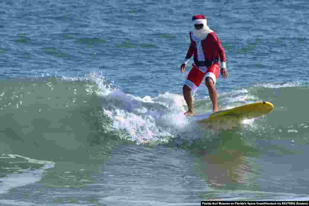 Mikulásruhába öltözve szörfözik egy férfi Florida egyik strandján december 23-án.