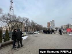 Представители акимата Алматы наблюдают за акцией протеста членов общественного объединения «Желтоксан акикаты». 26 декабря 2020 года.