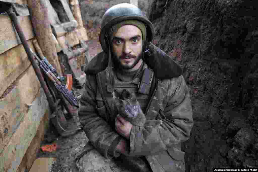 """Vitaliy, a soldier who goes by the call sign """"Hans,"""" holds a cat in a trench near Zhelobok in January 2020. Vitaliy first attempted to join the army in 2014, when he was just 16. After the military rejected him, the teenager waited two years before finally signing a contract to fight in 2016."""