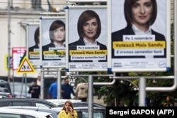 A woman walks past campaign posters for presidential candidate Maia Sandu in Chisinau on October 28.