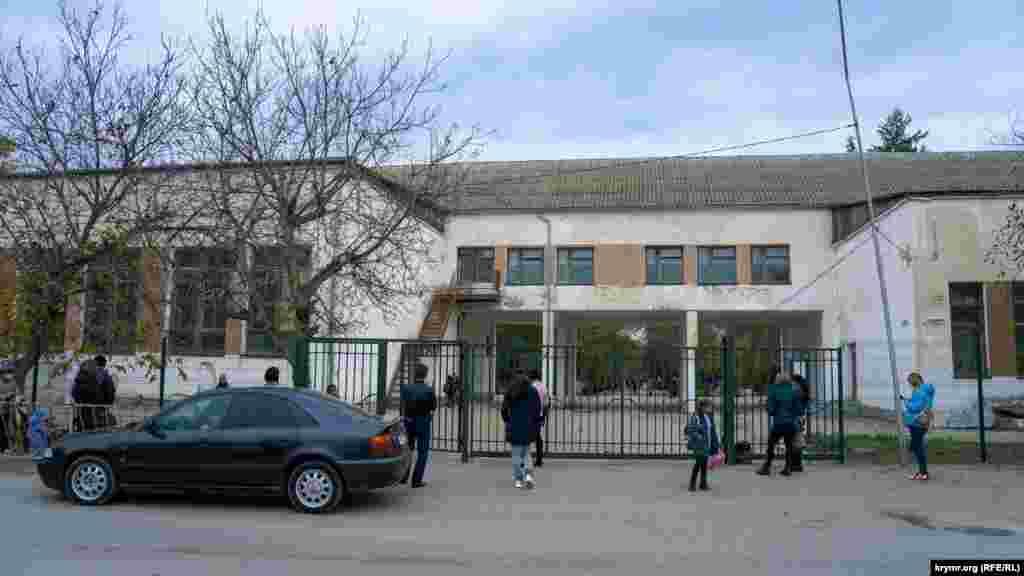 Батьки зустрічають своїх дітей-школярів у «зоні безпеки» середньої школи №1. На територію навчального закладу їм заходити заборонено