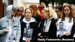 Fotografii ale unor politicieni și activiști de opoziție arătate de demonstranți în fața Teatrului Național Academic Janka Kupala, Minsk, 28 august 2020.