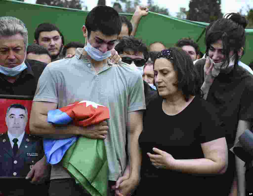 The son and widow of Azerbaijani Colonel Ilgar Mirzayev attend his funeral in Baku. Mirzayev was among five Azerbaijani soldiers killed in cross-border clashes on July 14.