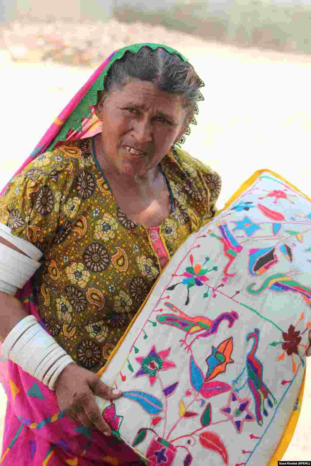Kallan Bibi holds a handmade pillow case featuring Tharparkar's traditional embroidery.