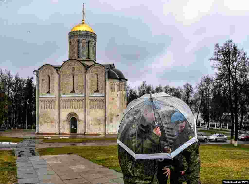 Российские кадеты прячутся от дождя под зонтиком у церкви во Владимире
