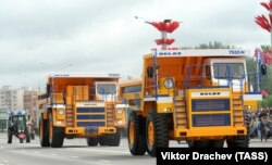 Two BelAZ quarry trucks rolling through Minsk during a military parade