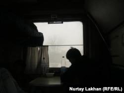 «Алматы - Защита» бағытымен жүретін 352-пойыздың жарығы жоқ плацкарт вагонында отырған жолаушылар. 26 қаңтар 2014 жыл.