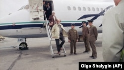 Aleksandr Solzhenitsyn, followed by his wife, Natalia, steps off a plane in Vladivostok and sets foot on Russian soil for the first time in 20 years in May 1994.