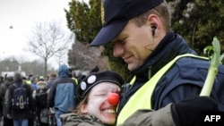 An activist wearing a red nose hugs a policeman during a protest in Copenhagen on December 16.