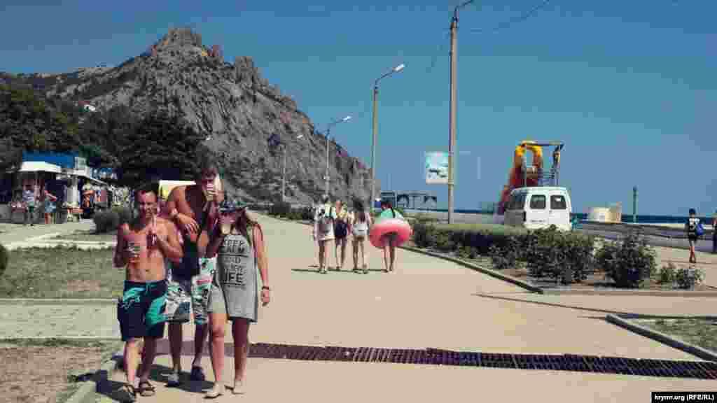 Отдыхающие прогуливаются по набережной и пьют пиво. На горизонте гора Кара-Даг