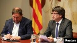 Каталония аймағының бұрынғы премьер-министрі Карлес Пучдемон (оң жақта) мен бұрынғы вице-президенті Ориол Жункерас.