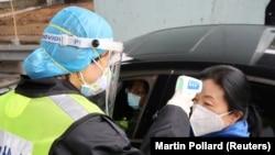 یک مقام بهداشتی در حال معاینه مسافران در استان هوبئی چین.
