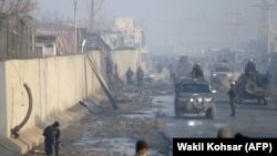 Afghan security forces gather at the site of a powerful truck bomb attack a day after it detonated near a foreign compound in Kabul on January 15.