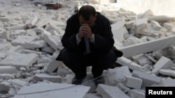 Чоловік сидить на руїнах будинку в сирійському Алеппо, 6 лютого 2014 року