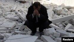 Чоловік на руїнах будинку в сирійському Алеппо, 6 лютого 2014 року