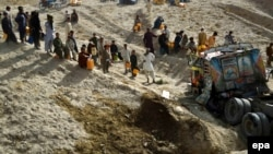 Pakistan -- Pakistanis try to collect leaking oil from the wreck of a tanker destined for NATO forces in Afghanistan, which overturned on a road on the Pakistan-Afghan border, near Chaman, Pakistan, 04 August 2015