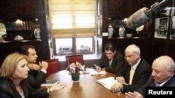 ისრაელის საგარეო საქმეთა მინისტრი ციპი ლივნი (მარცხნივ) და პალესტინის ყოფილი პრემიერ-მინისტრი აჰმედ ყურეი (მარჯვნივ) და პალესტინელთა დელეგაციის ერთ-ერთი ხელმძღვანელი საებ ერექათი (მარჯვნიდან მეორე) მოლაპარაკებებზე იერუსალიმში. 2008 წლის 27 მაისი.