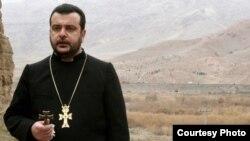 Իրան - Հայ հոգևորականն աղոթում է Իրան-Ադրբեջան սահմանին, իսկ հետին պլանում երևում է, թե ինչպես են ադրբեջանցի զինվորները ոչնչացնում հայկական խաչքարերը, 2005թ. (Լուսանկարը՝ Djulfa.com-ի)