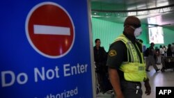 U.S. -- An airport worker wears a protective face mask in the arrivals area of the Los Angeles International Airport as the US announced increased passenger screenings against the Ebola Virus on October 9, 2014.