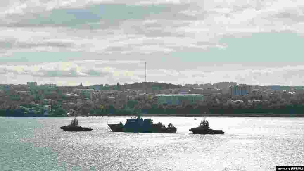 Вид с северского холма на Севастопольскую бухту, по которой два буксира тянут маленький военный корабль