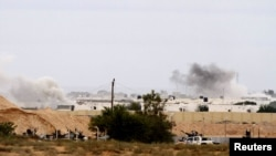 NTC fighters stand guard during heavy fighting as they push forward towards the center of Sirte on October 7.