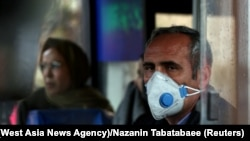 An Iranian man wears a protective masks to prevent contracting coronavirus on a bus in Tehran on February 25.