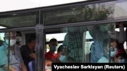 Ашхабодда автобусда кетаётган одамлар.