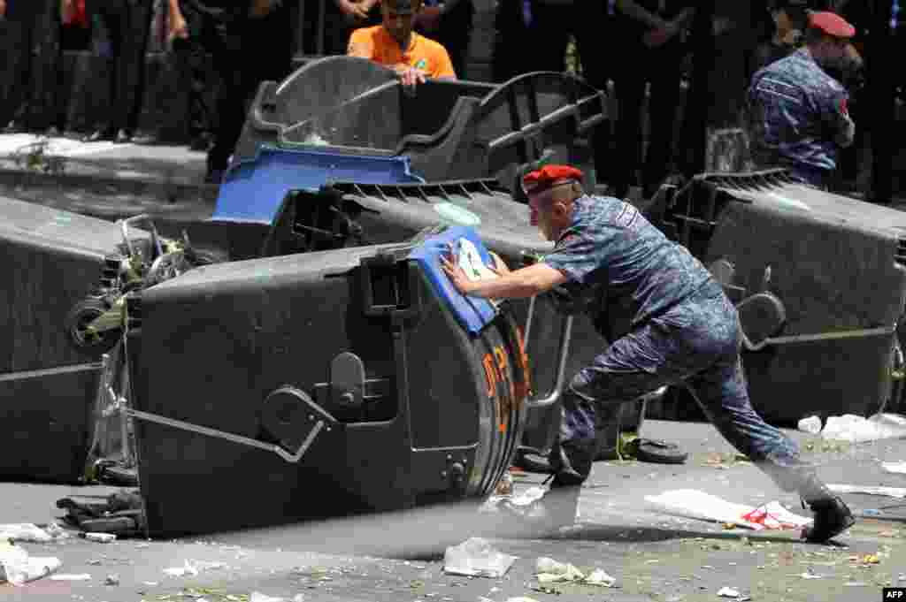 Armenian police officers remove barricades erected by demonstrators protesting against electricity price hikes in central Yerevan on July 6. (AFP/Photolure/Vahram Baghdasarian)