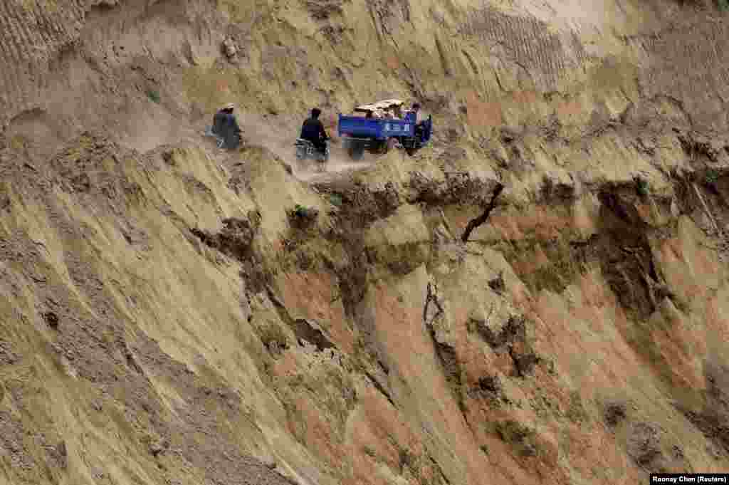 Motorcycles and a truck travel on a road near a cliff at a landslide site after a 6.6-magnitude earthquake hit China's Gansu Province. The death toll from two earthquakes in the province has climbed to 95. (Reuters/Rooney Chen)