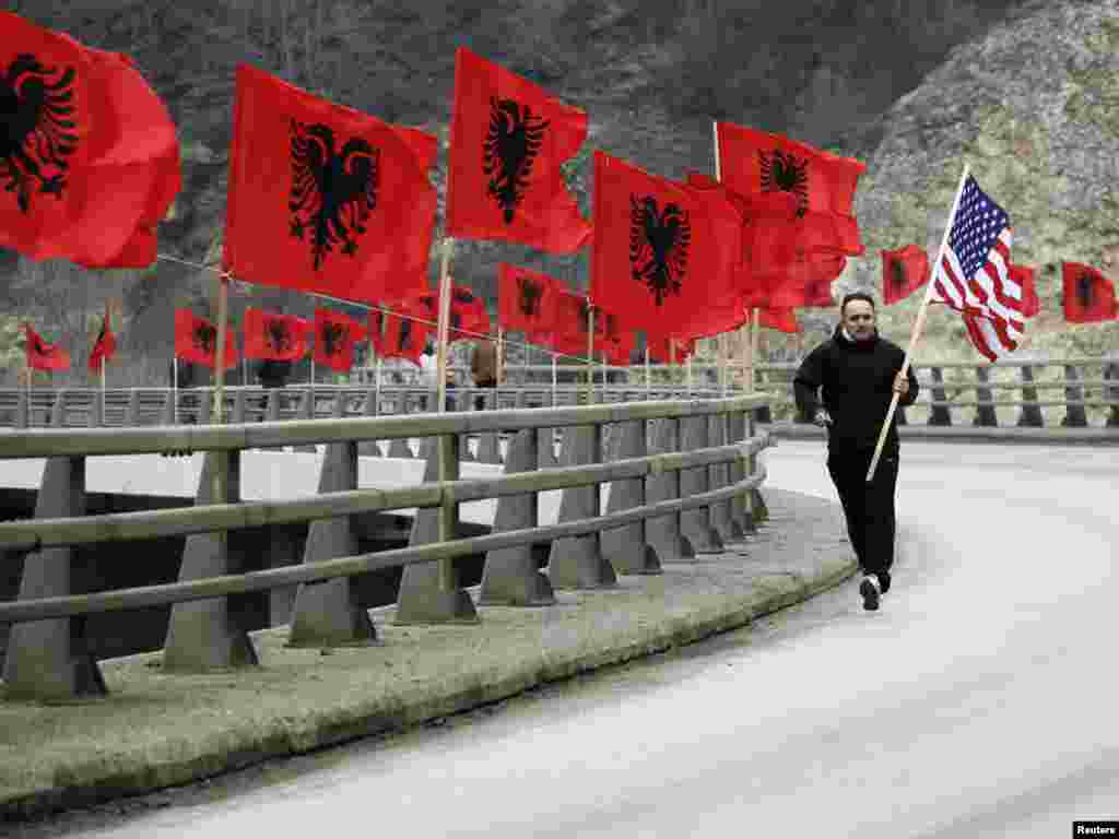 An ethnic Albanian man holding a U.S. flag jogs down a road lined with Albanian national flags in the town of Kacanik, Kosovo, on February 16, one day before Kosovo celebrated the third anniversary of its declaration of independence from Serbia. (Reuters/
