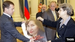 Human rights activist Svetlana Gannushkina gives Russian President Dmitry Medvedev a portrait of slain human rights activist Natalia Estemirova during a meeting at the Kremlin in Moscow in November 2009.