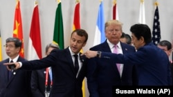 از راست: شینزو آبه، دونالد ترامپ و امانوئل مکرون پیش از نشست کاری سران گروه ۲۰ در ژاپن