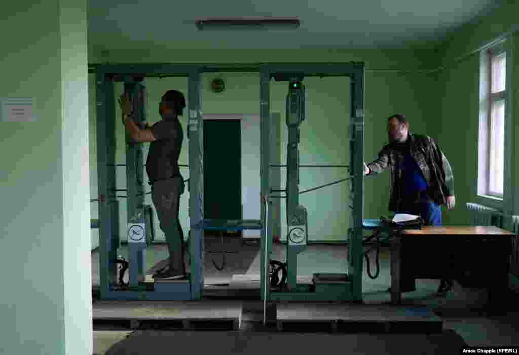 "This is the moment every visitor to Chernobyl dreads. As fixer Dmitriy Kolchinskyy (left) is tested for radiation, the alarm sounds. The red light blinking in front of him indicates contamination on his chest area. After he whips off  his visitor's badge the result is clean. But he passes through three different scanners to be sure, then on the way home he calls his wife to arrange a complete change of clothes. The T-shirt will be thrown away. ""I don't want that stuff anywhere near my kid."" A stark reminder that despite the time that has passed and despite the optimism of people like Vasyl, Chernobyl remains a poisoned land."